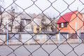 Rusty steel chain link or wire mesh as boundary wall. There is yard to the house with a red roof behind the mesh.