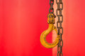 Rusty Yellow Hook and chains with red background Royalty Free Stock Photo