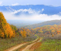 Rut road in autumn forest against mountains clouds background Royalty Free Stock Images