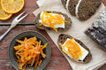Rye bread with butter and homemade orange confiture on rusted wo breakfast wooden table Royalty Free Stock Photography