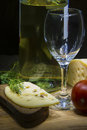 Rye bread with cheese wine bottle and empty glass still life of on green parsley of wineglass on wooden surface over black Stock Images