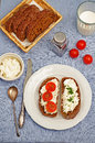 Rye bread with cream cheese and dill and tomato on a blue background tinting selective focus Royalty Free Stock Images