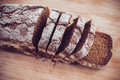 Rye bread a loaf of fresh rustic wholemeal sliced ​​on a wooden board close up Stock Photography