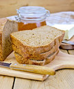 Rye homemade bread stacked with honey on a board stack of slices of knife plate napkin loaf of jar of wooden Royalty Free Stock Image