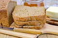 Rye homemade bread stacked with honey and knife a stack of slices of a on a plate napkin loaf of a jar of butter on wooden board Stock Photography