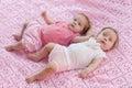 Süße kleine zwillinge die auf einer rosa decke liegen Stockfotos