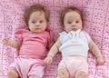 Süße kleine zwillinge die auf einer rosa decke liegen Lizenzfreie Stockbilder