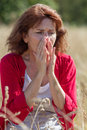 50s brunette woman having pollen allergies in field Royalty Free Stock Photo