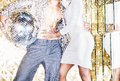 70s disco style couple posing with mirror ball Royalty Free Stock Photo