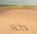 S o s written in the sand with a finger or stick Royalty Free Stock Photo
