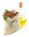 Sack of flax seeds and glass bottle of oil with leaves macro view in isolated on white background Stock Photography