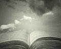Sacred reading detail of an old holy bible open with a beautiful and mystical sky in the background in black and white Royalty Free Stock Photos