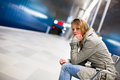 Sad and alone in a big city depressed young woman sitting metro station feeling sorrow regret Stock Photography