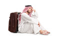 Sad arabic man sitting on the floor with a bag behind his back isolated white background Royalty Free Stock Photos