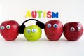 Sad autism apple series four apples are lined up in a row of the apples are red an is green the green is wearing headphones Stock Photo