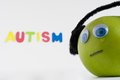 Sad autism apple series this is a green with the green is wearing ear phones in order to control its sensory input the green is Royalty Free Stock Image