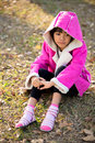 Sad beautiful little girl in pink coat looks down on background of autumn park Royalty Free Stock Photography