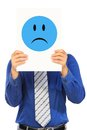 Sad and blue a man in shirt tie holding a signboard with a emoticon over his face Stock Images