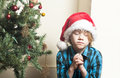 Sad boy praying at christmas small young the tree Royalty Free Stock Image