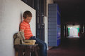 Sad boy sitting on bench by wall in corridor Royalty Free Stock Photo