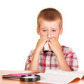 Sad boy sitting at table, notebook, pencils, magnifying glass isolated . Royalty Free Stock Photo