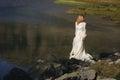 Sad bride posing in a mountain lake Royalty Free Stock Photo