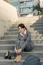 Sad business woman feel helpless and sit on stairs in modern city Stock Image