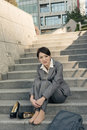 Sad business woman feel helpless and sit on stairs in modern city Stock Photography