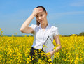 Sad business woman in flower field outdoor with clipboard touch head. Young girl in yellow rapeseed field. Beautiful spring landsc Royalty Free Stock Photo