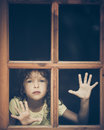 Sad child looking out the window Royalty Free Stock Photo