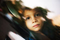 Sad child looking through window leaving by car the Royalty Free Stock Photography