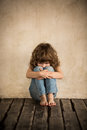 Sad child siiting on the floor in dark room Royalty Free Stock Photos