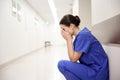 Sad or crying female nurse at hospital corridor