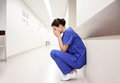 Sad or crying female nurse at hospital corridor Royalty Free Stock Photo