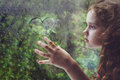 Sad curly little girl looking out the rain drop window Royalty Free Stock Photo