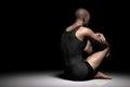 Sad, depressed man sitting alone on floor in dark spotlight. Depression, pain Royalty Free Stock Photo