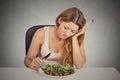 Sad displeased young woman eating salad Royalty Free Stock Photo