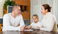 Sad family of three with documents at home Royalty Free Stock Images