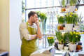 Sad florist man or seller at flower shop counter people sale retail business and floristry concept with cashbox standing Stock Image