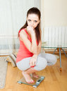 Sad girl  on bathroom scales Royalty Free Stock Photo