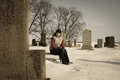 Sad girl in the graveyard a beautiful sitting front of a tomb stone at winter Stock Image