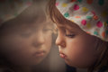 Sad girl looking through the window reflection of a little baby Royalty Free Stock Photos