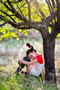 Sad girl with pigtails under the tree Royalty Free Stock Photo