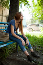 Sad girl sitting on a park bench Royalty Free Stock Photography