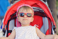 Sad girl in stroller sunglasses red Stock Photography