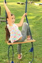 Sad girl on swing in t shirt with colorful butterflies grey pants and pink shoes sitting Stock Image