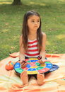 Sad girl with target litting little barefoot playing a colorful Royalty Free Stock Photos
