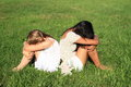 Sad girls sitting on grass Royalty Free Stock Photo
