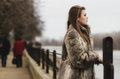 Sad glamorous brunette lady watching river portrait of the in expensive fur coat Royalty Free Stock Images