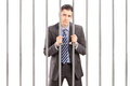 Sad handcuffed businessman in suit posing in jail and holding ba bars isolated on white background Stock Photos